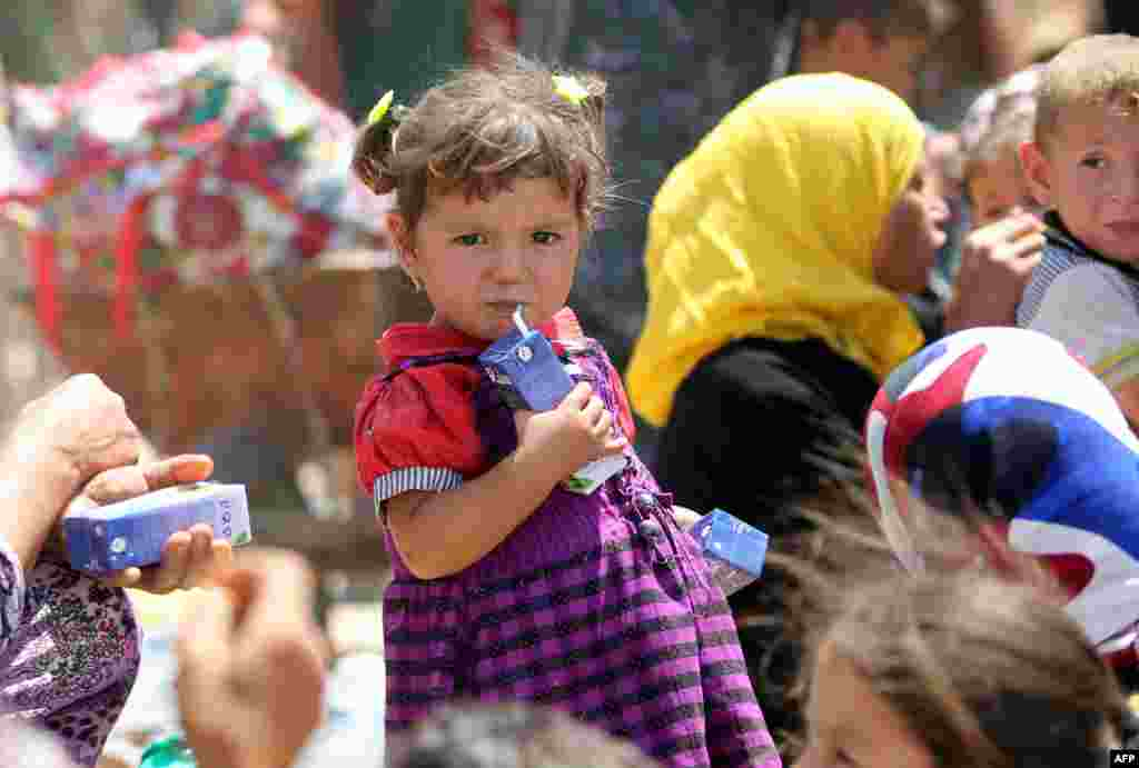 An Iraqi girl drinks juice near al-Sejar village, in Iraq's Anbar province, after fleeing with her family the city of Fallujah during a major operation by Pro-government forces to retake the city of Fallujah, from the Islamic State (IS).