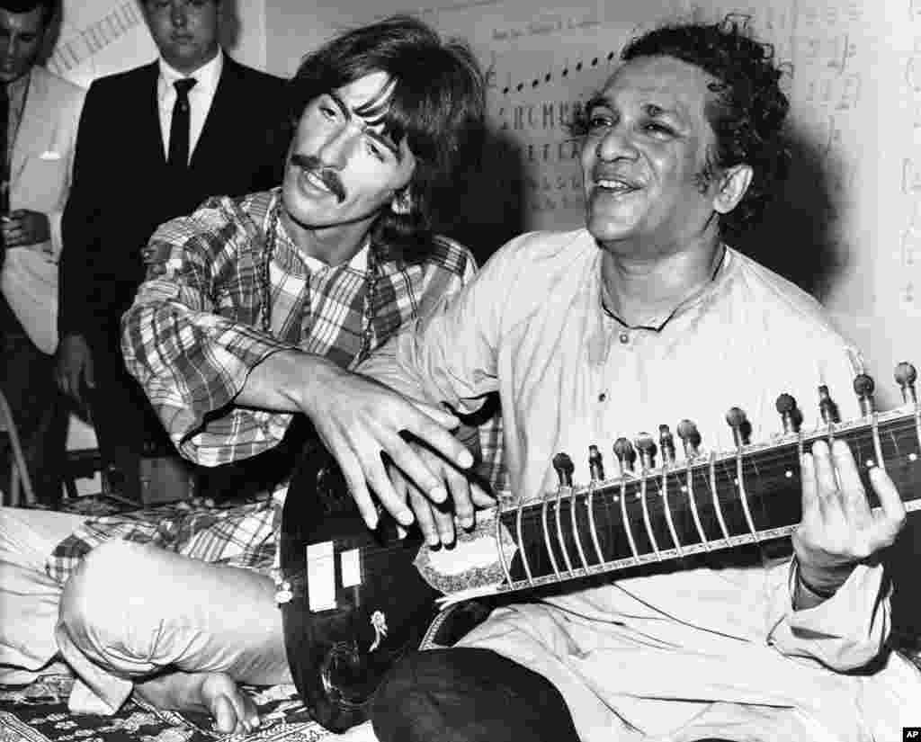 In this August 3, 1967 file photo, George Harrison, of the Beatles, left, sits with Ravi Shankar in Los Angeles, California as Harrison explains to newsmen that Shankar is teaching him to play the sitar.