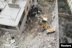 ພວກຄົນງານ ຂອງໜ່ວຍປ້ອງກັນພົນລະເຮືອນ ພວມຍ້າຍສົບຄົນຕາຍ ອອກຈາກ ຊາກຫັກພັງ ລຸນຫລັງການໂຈມຕີທາງອາກາດ ໃສ່ບ້ານ Kafr Hamra ໃນເຂດຊົນນະບົດ ຂອງແຂວງ Aleppo.