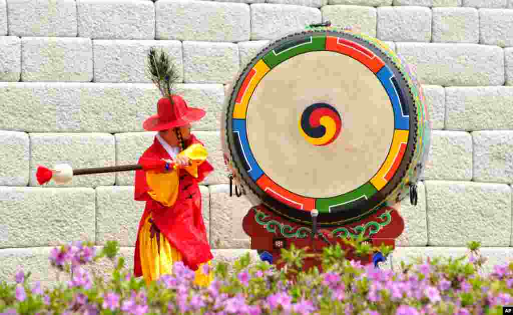 A South Korean traditional gate guard beats a drum during the reopening ceremony of landmark Sungnyemun gate in Seoul. Five years after an arsonist destroyed it, the stone-and-wood southern gate to the old walled capital of Seoul has been painstakingly restored to its late 14th century glory by a small army of master craftsmen using traditional tools.