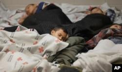 Niños detenidos en la frontera duermen en una celda de retención en una instalación de procesamiento de inmigrantes ilegales en Brownsville, Texas. Junio 18, 2014.