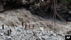 Aliran air sungai di Govindghat, India terlihat sangat deras dan bergolak di saat para relawan dan tentara paramiliter India berdiri mengamati jembatan darurat yang hancur diterjang banjir (22/6). Rusaknya jembatan tersebut menghambat proses evakuasi para korban, yang dilaporkan mencapai hampir 600 orang.