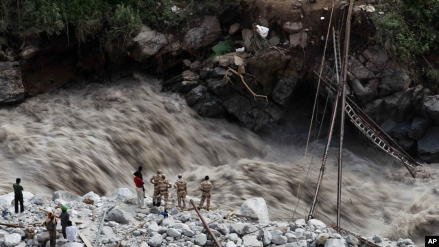 Water gushes down a river as Indian paramilitary soldiers and volunteers stand near a makeshift bridge after it was damaged hampering to evacuate the stranded pilgrims in Govindghat, India, June 22, 2013.