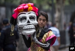 A woman walks before her performance in the Day of the Dead parade on Reforma avenue in Mexico City, Oct. 27, 2018.