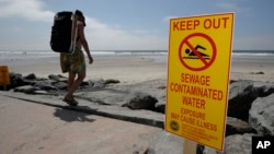 FILE - A beachgoer walks past a sign posted to warn people of contaminated water at Torrey Pines State Beach in San Diego, California.