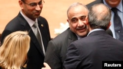 Iraq's new Oil Minister Adel Abdul-Mehdi, front facing, greets Iranian Ambassador to Iraq Hassan Danaifar, right, during a parliamentary session to vote on Iraq's new government at the parliament headquarters in Baghdad, Sept. 8, 2014.