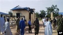 보코 하람 무장대원들의 공격을 받은 마을을 나이지리아 정부 관리들이 돌아보고 있다.