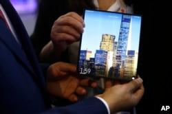 បុរសម្នាក់កាត់ទូរស័ព្ទ Huawei សេរី Mate X foldable 5G ក្នុងកម្មវិធី Mobile World Congress នៅទីក្រុង Barcelona ប្រទេស អេស្ប៉ាញ ថ្ងៃទី២៦ ខែកុម្ភៈ ឆ្នាំ២០១៩។ (AP)