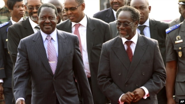 Kenya's PM Raila Odinga (l) walks with Gilbert Ake, named Prime Minister in the cabinet of Ivory Coast's incumbent leader Laurent Gbagbo, after arriving at the Felix Houphouet Boigny international airport in Abidjan, 03 Jan 2011.