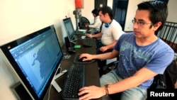 "Colombian systems programmer Juan Pico works on the video game ""Adios a las Armas"" (Farewell to Arms) in Bogota, Sept. 4, 2014"