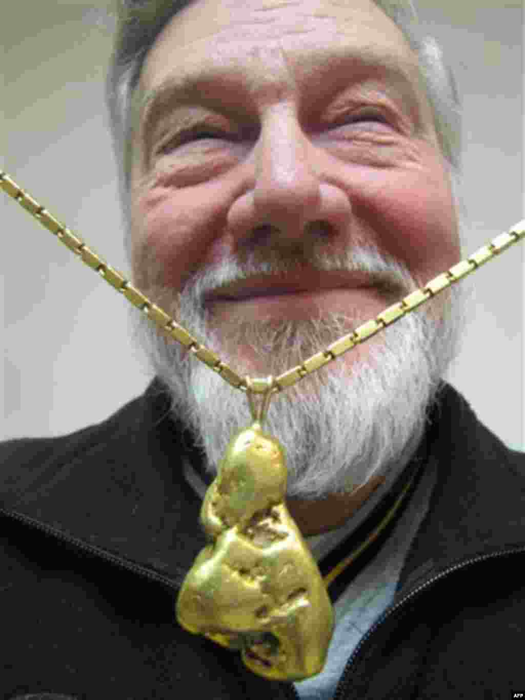 "In this Nov. 17, 2011 photo, Bill Dunlevy poses in Anchorage, Alaska, with his prized find, a 5 ounce piece of gold he found while prospecting and turned into a necklace. Dunlevy says it's the lure of the gold, what he calls ""gold fever"" that causes him a"
