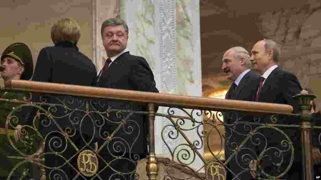 German Chancellor Angela Merkel, left back to a camera, Ukrainian President Petro Poroshenko, second left, Belarusian President Alexander Lukashenko, second right, and Russian President Vladimir Putin, walk together to continue their peace talks in Minsk.