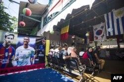 Para pemilih menunggu giliran memberikan suara dalam pilkada di sebuah TPS bertema Piala Dunia di Surabaya, 27 Juni 2018. (Foto: AFP)