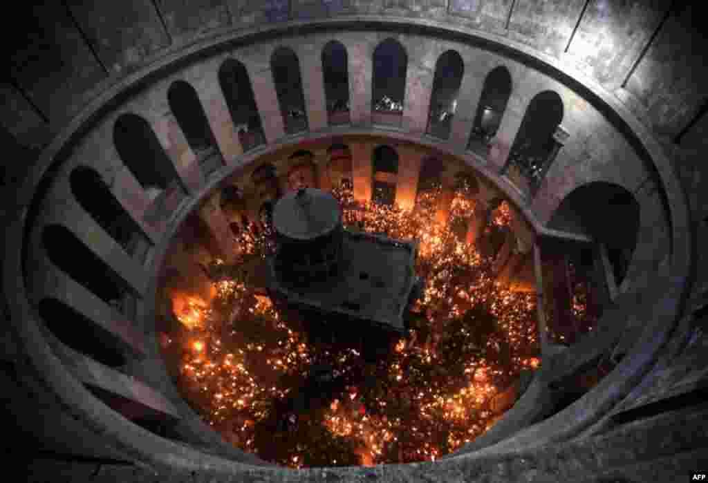 هزاران عبادت کننده مسیحی ارتدوکس با بهدست گرفتن شمعهايی که با شعله «آتش مقدس» میسوزند در کلیسای مقبره مقدس در شهر قدیمی اورشلیم در مراسم ارتدکس عید پاک موسوم به «آتش مقدس» - ۲۲ فروردين ۱۳۹۴ (۱۱ آوريل ۲۰۱۵)