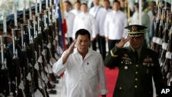 Philippine President Rodrigo Duterte, left, salutes during departure honors at Manila's International Airport, Philippines on Wednesday, Nov. 9, 2016.