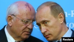 Russian President Putin listens to former President of the Soviet Union Gorbachev during news conference in Schleswig, Germany, December 21, 2004.