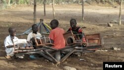 FILE - Children play with a broken playground chair in Kakuma refugee camp in northwestern Kenya.