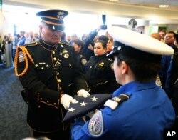 """一名洛杉矶机场警员把""""国家荣耀旗帜""""交给交通安全局仪仗队员,纪念被枪杀的安检员贺南德兹。"""