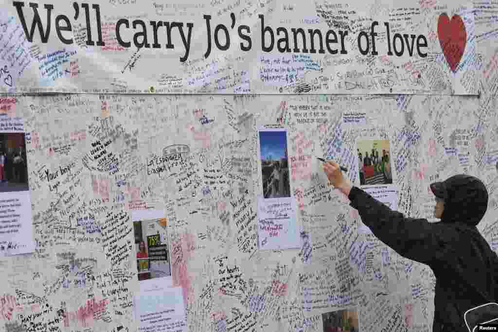 A man writes a tribute on a message board erected in memory of Labour Party MP Jo Cox, who was shot dead in Birstall, at Parliament Square in London, Britain.
