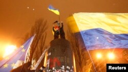 People climb up to the top of a pedestal after a statue of Soviet state founder Vladimir Lenin was toppled by protesters during a rally organized by supporters of EU integration in Kyiv, December 8, 2013.