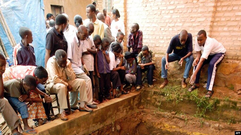 Les habitants de Nyamirambo déterrent les restes humains d'une fosse commune datant du génocide de 1994, à Kigali, le 05 avril 2004.
