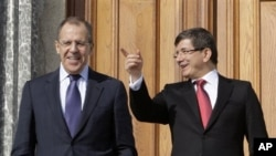 Russian Foreign Minister Sergey Lavrov, left, and his Turkish counterpart Ahmet Davutoglu pose for cameras after a news conference in Istanbul, Turkey, 20 Jan 2011