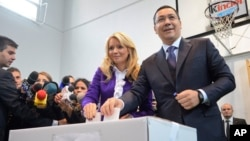FILE - Romanian Prime Minister and candidate of the ruling Social Democracy Party (PSD), Victor Ponta, right, casts his ballot alongside his wife, Daciana Sarbu, in Bucharest, Romania, Nov. 2, 2014.
