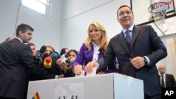 Romanian Prime Minister and candidate of the ruling Social Democracy Party (PSD), Victor Ponta, right, casts his ballot alongside his wife, Daciana Sarbu, in Bucharest, Romania, Nov. 2, 2014.