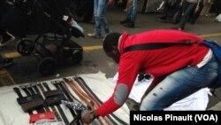 Un vendeur sénégalais installe sa marchandise au marché de Lima, Milan, 10 octobre 2015 (Nicolas Pinault/VOA)