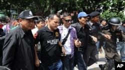 Thai Red Shirt anti-government protest leaders Nattawut Saikuar (2L) and Wiphuthalang (3R, blue cap) are arrested by police officers after they announced to the crowd their surrender on the stage inside the protesters' camp in downtown Bangkok, 19 May 201