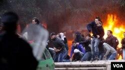 Para demonstran melemparkan batu ke arah polisi di Tirana, Albania, Jumat (21/1).