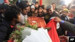 Kerabat pemimpin oposisi Tunisia Chokri Belaid menggotong peti mati berisi jenazahnya sebelum pemakaman (8/2). (AP/Amine Landoulsi)