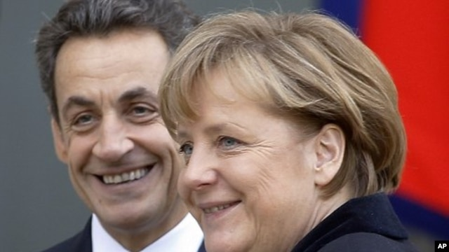 French President Nicolas Sarkozy, left, smiles as he greets German Chancellor Angela Merkel prior to their meeting at the Elysee Palace in Paris, December 5, 2011.