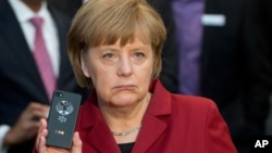 """Foto de archivo de Angela Merkel mostrando un Blackberry a prueba de escuchas. Ahora exige un acuerdo de """"no espionaje"""",."""
