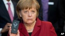 2013年3月5日德国总理默克尔在汉诺威电脑展展示防窃听黑莓手机 (资料照片)