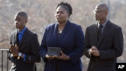 FILE - Isatu Salia carriers the cremated remains of her husband, Ebola victim Dr. Martin Salia, while their sons Maada Martin Salia, 20, right, and Hinwaii Sakatty Salia, 12, walk with her to enter St. Mary's Church in Landover Hills, Md., for a funeral Mass, Nov. 29, 2014.
