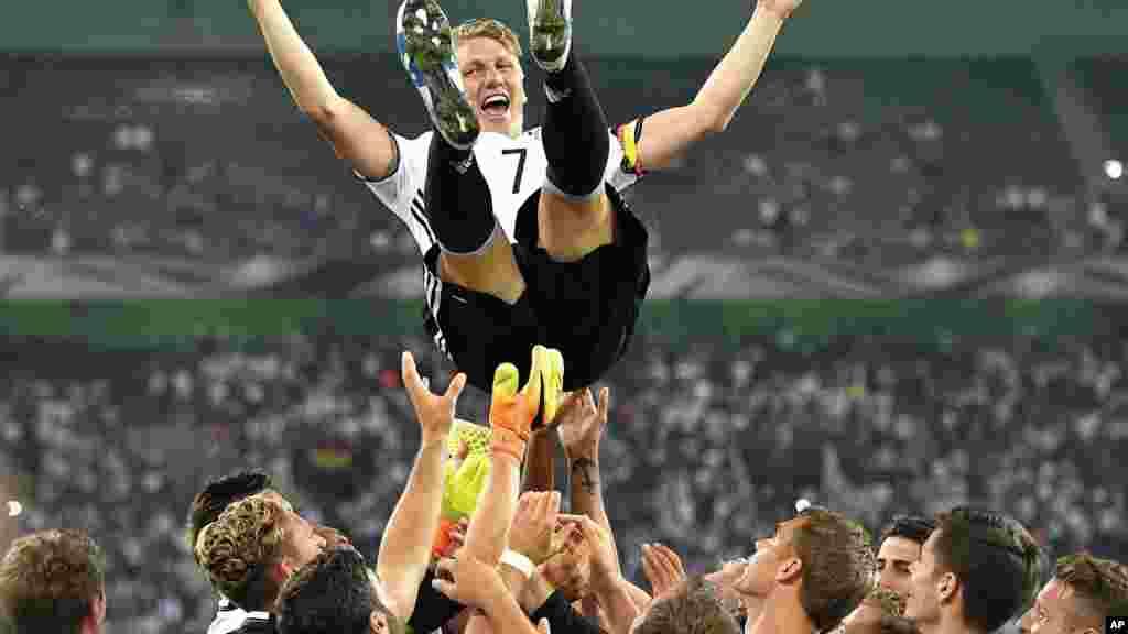 L'équipe nationale de football de l'Allemagne lance son capitaine Bastian Schweinsteiger dans l'air après avoir joué son dernier match pour l'équipe nationale à Moenchengladbach, en Allemagne, le 31 août2016.