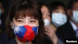 台灣桃園一家製造用於防疫口罩的醫用無紡布工廠的職工戴著印有台灣旗幟的口罩。 (2020年3月30日)