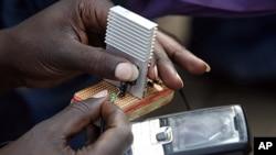 一位肯尼亞的電機工程學生在顯示與自行車相連接的充電器如何為手機充電