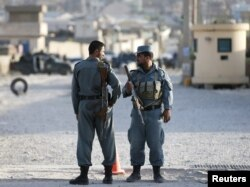 Afghan policemen keep watch at the site of an attack after an overnight battle outside a base in Kabul, Afghanistan, Aug. 8, 2015.