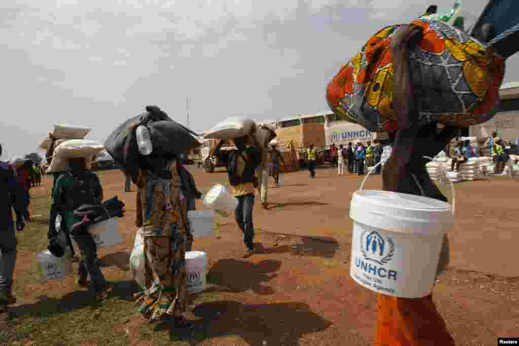 People displaced by the recent unrest collect food distributed by aid agencies at an IDP camp at the Mpoko international airport of Bangui, Feb. 12, 2014.