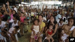 Filipino women and their children participate in a family planning fair to commemorate World Population Day in Manila, Philippines, July 11, 2012.