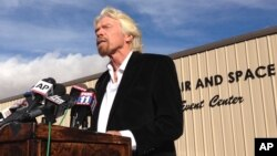 FILE - Billionaire Virgin Galactic founder Richard Branson salutes the bravery of test pilots during a news conference in Mojave, Calif., Nov. 1, 2014. Virgin Galactic announced a new version of its space tourism rocket.