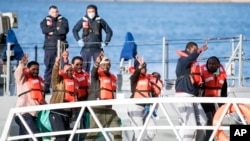 Migrants wave and give the v-sign as they disembark at Hay Wharf, Pieta, Malta, Jan. 9, 2019.