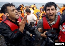 A Greek Red Cross volunteer comforts a crying Syrian refugee moments after disembarking from a flooded raft at a beach on the Greek island of Lesbos after crossing a part of the Aegean Sea from the Turkish coast by an overcrowded raft, Oct. 20, 2015.