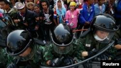 在曼谷城外,抗議者在總理英祿開會的政府建築外集結,軍人持盾守衛。