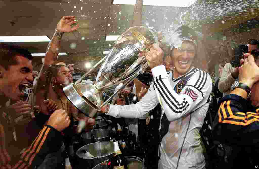 Beckham is sprayed with champagne as the LA Galaxy celebrate defeating the Houston Dynamo 3-1 in the MLS Cup championship soccer game in Carson, Calif., December 1, 2012.