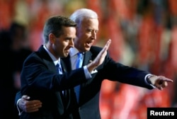 FILE - Attorney General Beau Biden (D-DE) (L) and Vice Presidential candidate Senator Joe Biden (D-DE) gesture on stage at the 2008 Democratic National Convention in Denver, Colorado August 27, 2008.