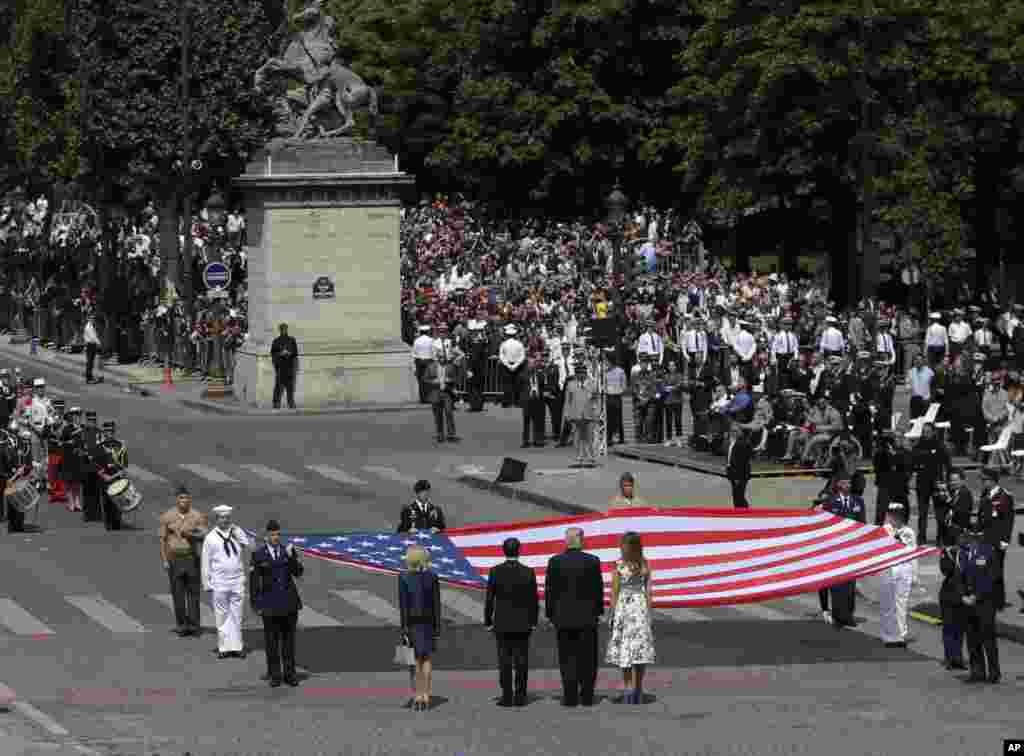 2017年7月14日,美国总统川普和夫人,法国总统马克龙和夫人,在巴黎国庆游行之后,站在巨大的美国国旗前面