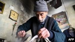 Abu Mahmoud (72), menggunakan alat setrika tua untuk menyetrika pakaian di tokonya di kota Idlib yang dikuasai pemberontak di barat laut Suriah, 28 Maret 2021. (Zein Al RIFAI / AFP)